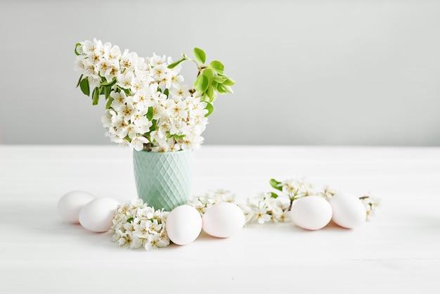 Białe pisanki i gałąź wiosna z kwiatami. wiosna wielkanoc kwiaty wiśniowe kwitnienie. wiosenne kwiaty. piękny sad. wiosna