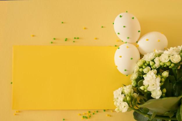 Białe pisanki w kropki na żółtym tle z bukietem kwiatów.
