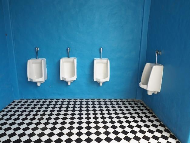 Białe pisuary w męskiej łazience
