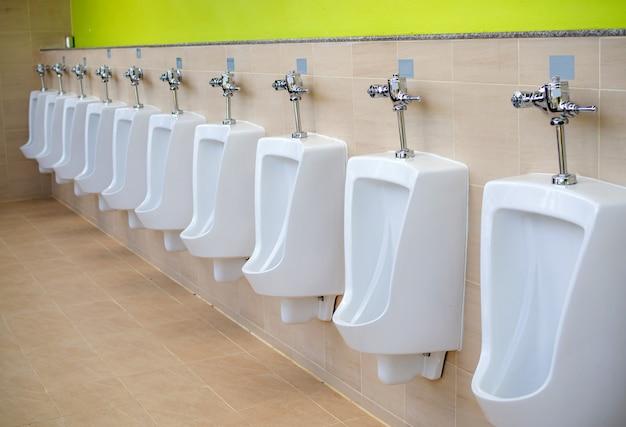 Białe pisuary w publicznej toalecie. wybierz fokus