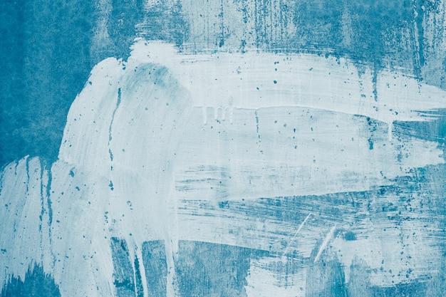 Białe plamy farby na niebieskiej betonowej ścianie.