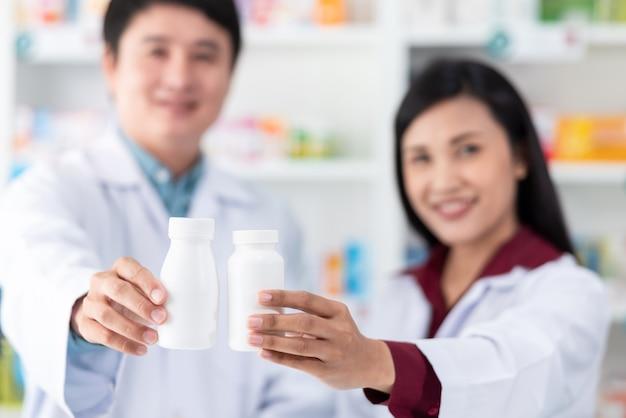 Białe plastikowe butelki leku na trzymanie ręki mężczyzny i kobiety farmaceuta azjatyckiego w aptece tajlandii z bliska i selektywnej ostrości