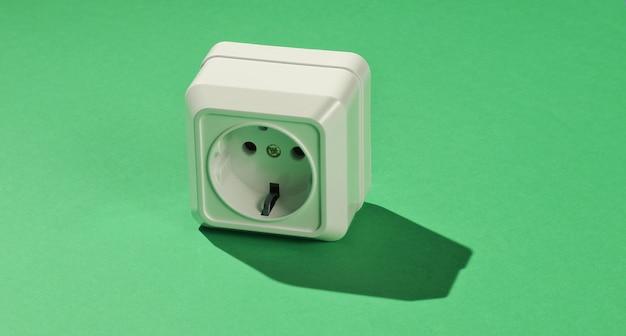 Białe plastikowe gniazdo zasilania na zielonym tle. minimalizm