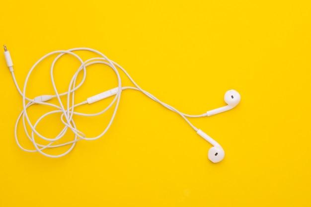 Białe, plątane słuchawki z widokiem z góry.
