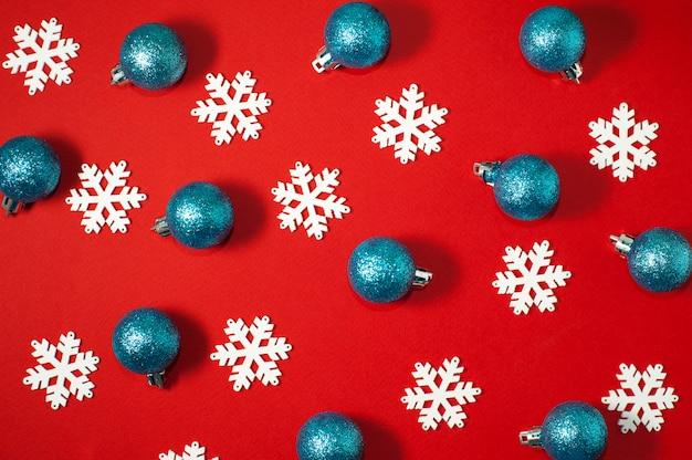 Białe płatki śniegu i niebieskie błyszczące bale sylwestrowe na czerwonym tle. zdjęcie ozdoby świąteczne