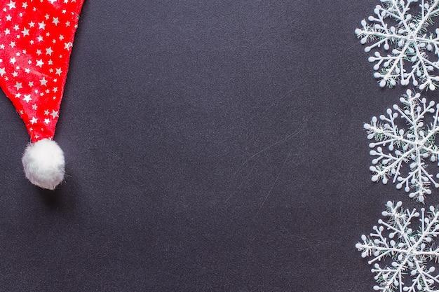 Białe płatki śniegu na czarnej tablicy.