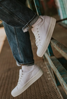 Białe płócienne trampki na modelu dżinsów