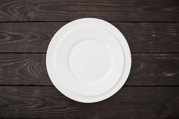 Białe płytki ceramiczne na starym ciemnym drewnianym stole