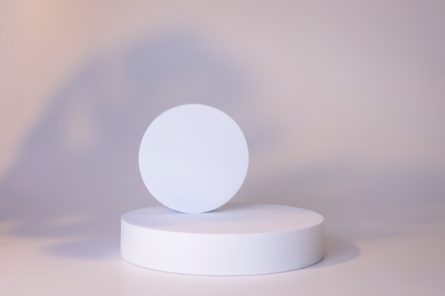 Białe podium na białym tle z cieniami liści. podium dla produktu, prezentacja kosmetyczna. kreatywna makieta. cokół lub platforma na kosmetyki. minimalistyczny design.
