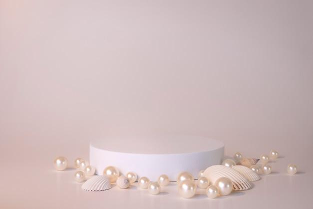 Białe podium na białym tle z perłami i muszlami. podium dla produktu, prezentacja kosmetyczna. kreatywna makieta. cokół lub platforma na kosmetyki. minimalistyczny design.