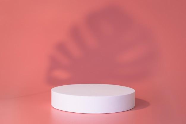 Białe podium na różowym tle z cieniami liści. podium dla produktu, prezentacja kosmetyczna. kreatywna makieta. cokół lub platforma na kosmetyki. minimalistyczny design.