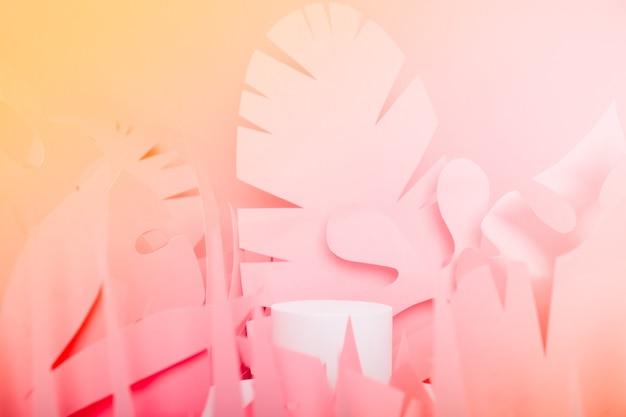 Białe podium w kształcie walca wśród papierowych liści tropikalnych. prezentacje podium dla produktów kosmetycznych. makiety na wystawy, prezentacja produktów,