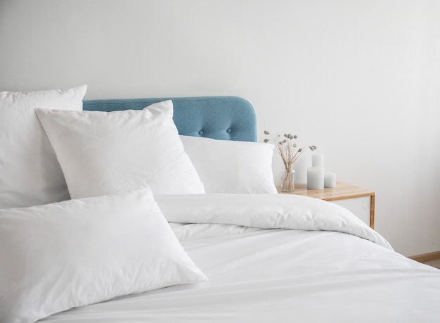 Białe poduszki i kołdra na niebieskim łóżku.