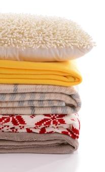 Białe poduszki i kolorowe pledy na białym tle