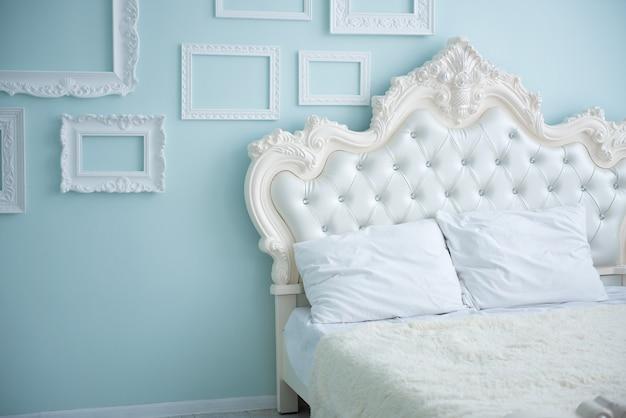 Białe poduszki na łóżku w stylu retro w sypialni z niebieskimi ścianami