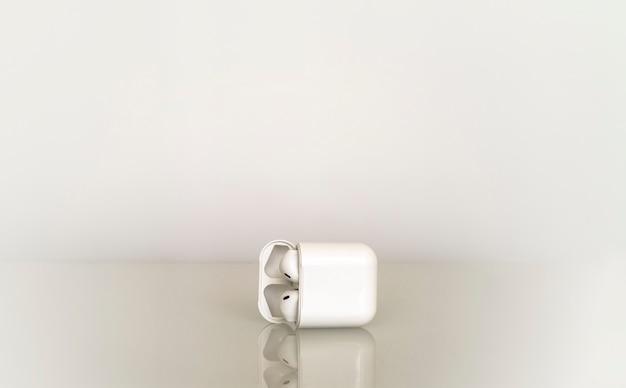 Białe pojedyncze słuchawki bezprzewodowe w polu ładowania na szarym gradiencie z odbiciem w szklance stołu