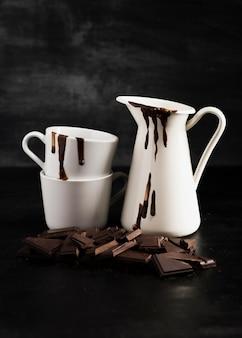 Białe pojemniki wypełnione rozpuszczoną czekoladą i kawałkami czekolady
