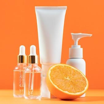 Białe pojemniki z kremem i pomarańczą