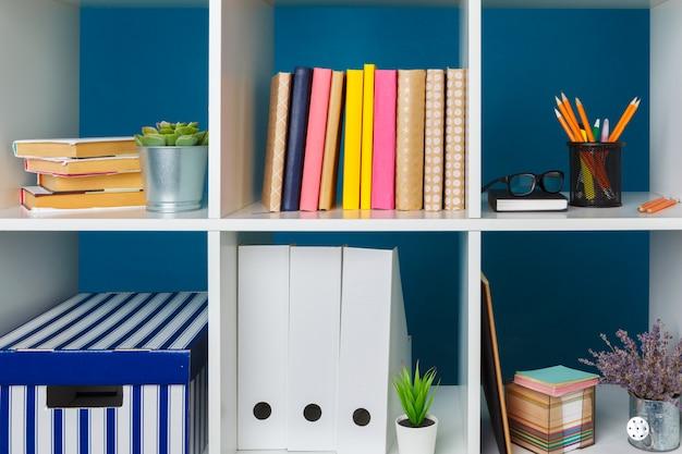 Białe półki biurowe z różnymi artykułami biurowymi