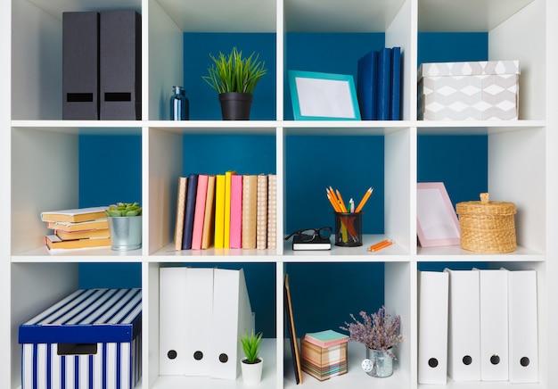 Białe półki biurowe z różnymi artykułami, z bliska