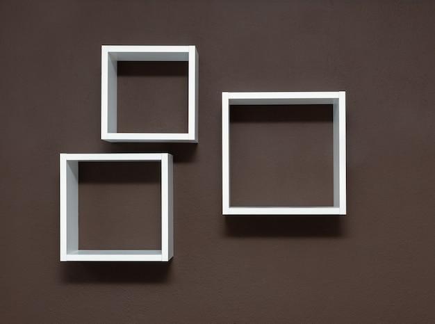 Białe półki na brązowym tle ściany