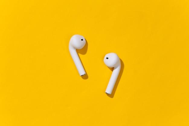 Białe prawdziwe bezprzewodowe słuchawki bluetooth lub wkładka douszna na jasnożółtym tle.