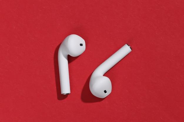 Białe, prawdziwe bezprzewodowe słuchawki bluetooth lub wkładki douszne na jasnoczerwonym tle