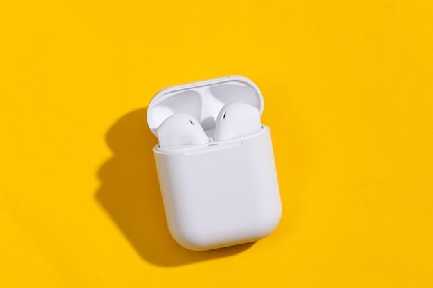 Białe prawdziwe bezprzewodowe słuchawki bluetooth lub wkładki douszne w etui ładującym na żółtym jasnym tle.