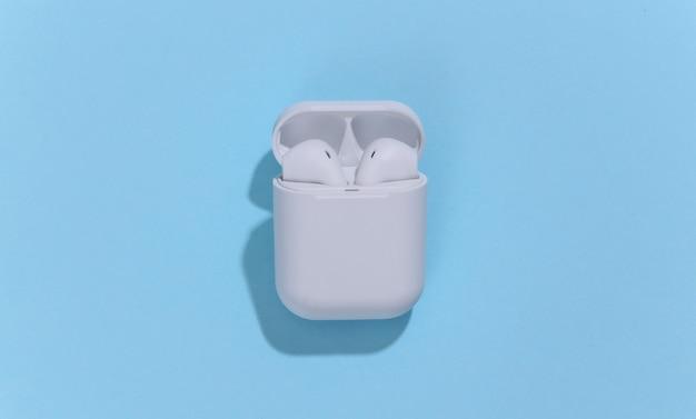 Białe prawdziwe bezprzewodowe słuchawki bluetooth lub wkładki douszne w etui ładującym