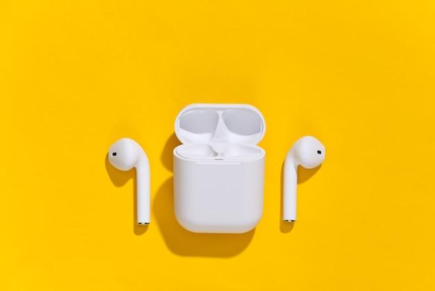 Białe prawdziwe bezprzewodowe słuchawki bluetooth lub wkładki douszne z etui ładującym na żółtym jasnym tle.