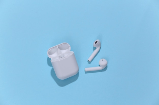 Białe prawdziwe bezprzewodowe słuchawki bluetooth lub wkładki douszne z etui ładującym
