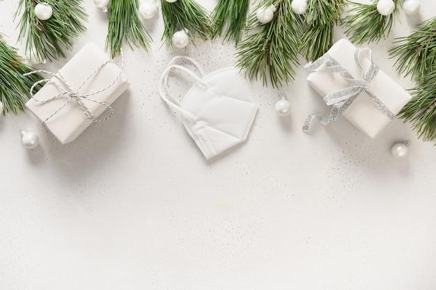 Białe prezenty świąteczne i dekoracje z maską medyczną i wiecznie zielonymi gałązkami