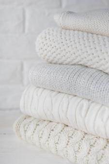 Białe przytulne swetry z dzianiny i koraliki na tle białej cegły ściany. miejsce na tekst.
