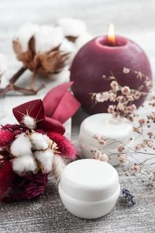 Białe pudełka kremu, zapalona świeca i bukiet suchych kwiatów marsala. układ spa na drewnianym stole