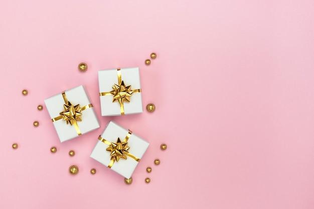 Białe pudełka prezentowe ze złotymi kokardkami i złotymi dekoracjami na pastelowym różowym tle. minimalistyczna kartka świąteczna w stylu. leżał na płasko, widok z góry, miejsce na kopię.