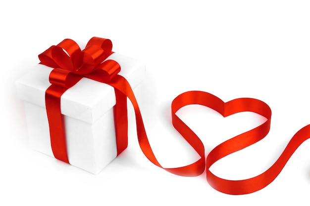 Białe pudełka z czerwonymi wstążkami i ozdobnym sercem