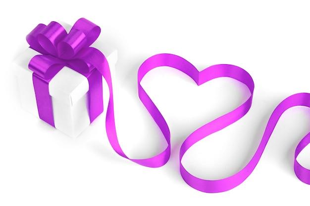 Białe pudełka z fioletowymi wstążkami i ozdobnym sercem