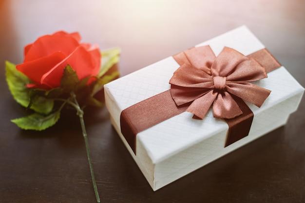 Białe pudełko i czerwona róża na drewnianym stole