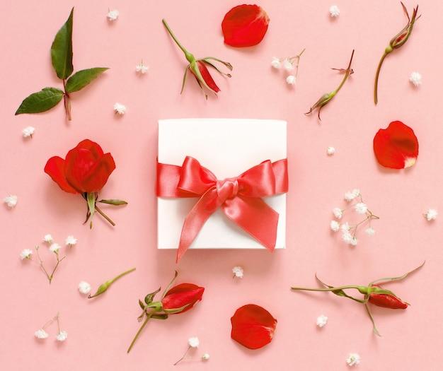 Białe pudełko i czerwone róże na jasnoróżowym tle widok z góry
