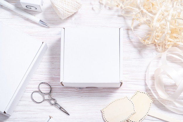 Białe pudełko kartonowe na drewnianym biurku, płaskie makieta