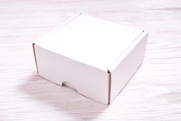 Białe pudełko kartonowe na drewnianym biurku