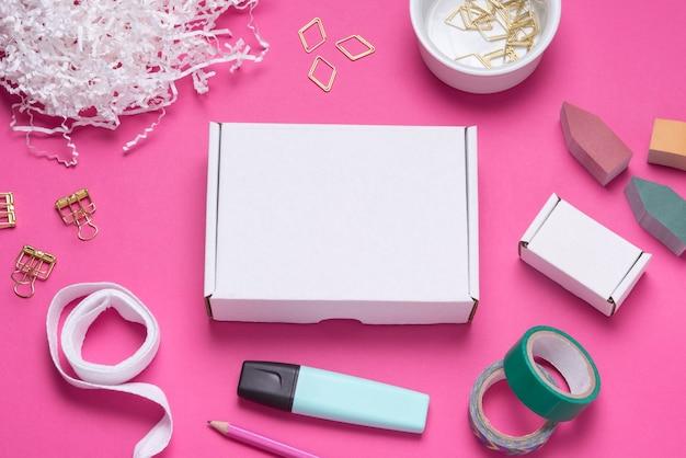 Białe pudełko kartonowe na kolorowym biurku