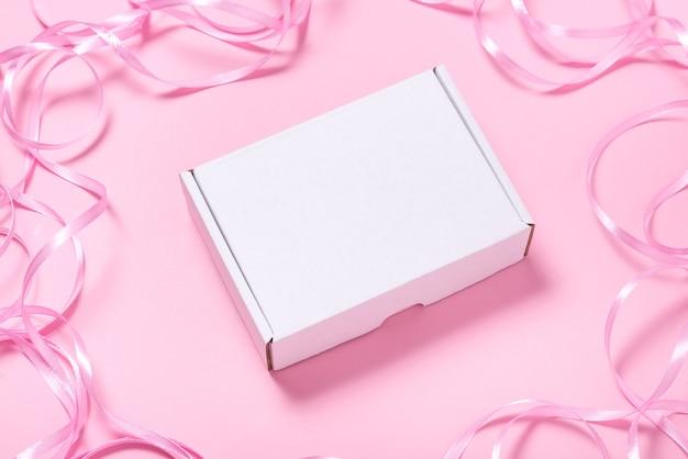 Białe pudełko kartonowe ozdobione różową wstążką