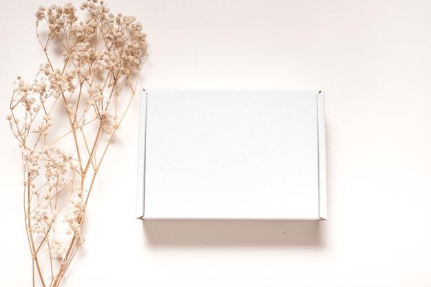 Białe pudełko kartonowe ozdobione suszoną trawą