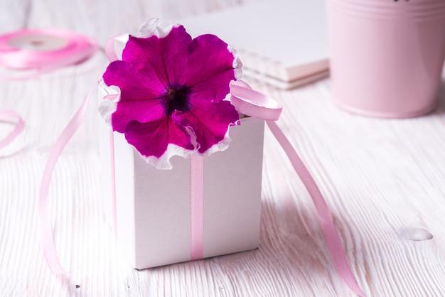 Białe pudełko kartonowe z kwiatkiem