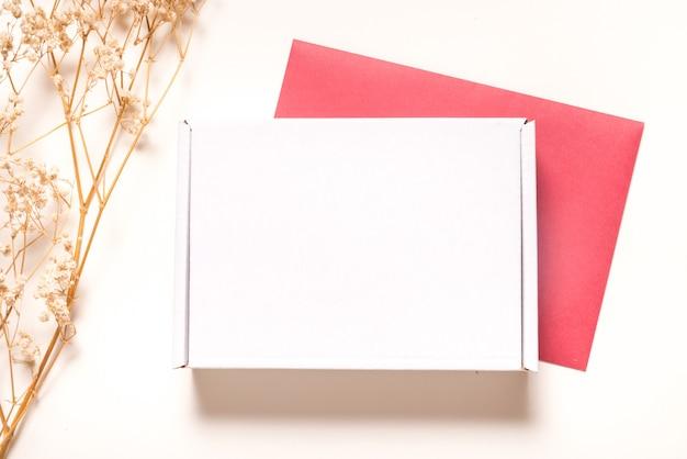 Białe pudełko kartonowe zdobione suszoną trawą, leżące na płasko