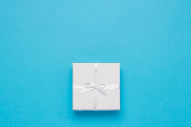 Białe pudełko na niebieskim tle. minimalistyczny styl. leżał płasko, widok z góry
