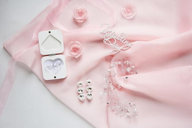 Białe pudełko na obrączki na różowym szyfonie z akcesoriami ślubnymi