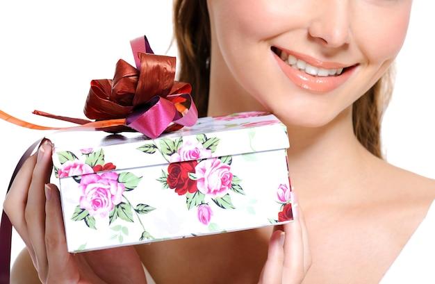 Białe pudełko na prezent z czerwoną wstążką trzymające dość nie do poznania kobietę