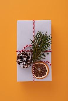 Białe pudełko upominkowe ozdobione czerwoną wstążką, gałązką jodły, szyszką i plasterkiem suszonej pomarańczy